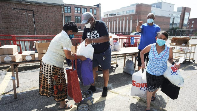 Volunteers Ray Yancey, center, and Cleveland Jackson, center-right, distribute food to Valadina Goncalves, left, and Claudina Goncalves, right, at a community food drive at Mount Moriah Baptist Church in Brockton, Saturday, Aug. 22, 2020.