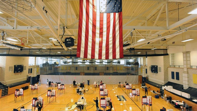 A large American flag hangs above the gymnasium at East Bridgewater Junior/Senior High School during voting for the Massachusetts primary election, Tuesday, Sept. 1, 2020. Voting booths were physically distant amid the ongoing coronavirus pandemic.