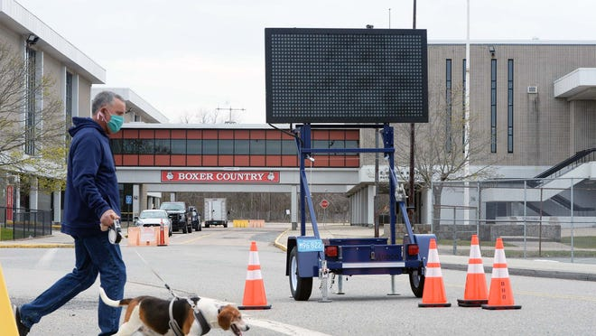 In an April 30, 2020, file photo, a man wearing a mask during the coronavirus pandemic walks his dog through the grounds of Brockton High School, where a drive-thru COVID-19 testing site was being set up.
