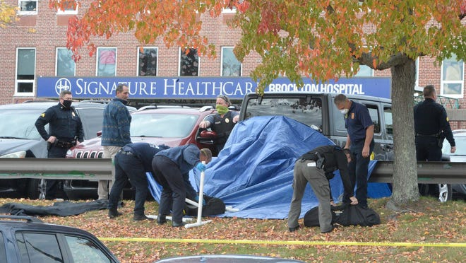 Police cover the scene with a tarp. A man died of a self-inflicted gunshot wound in the parking lot outside Signature Healthcare Brockton Hospital, Tuesday, Oct. 27, 2020.