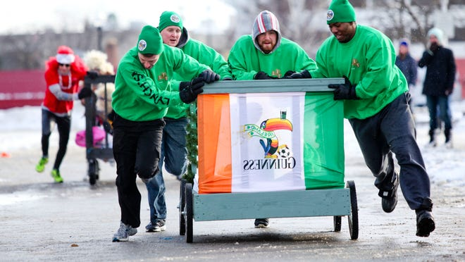 AJ Misch, left, Zachary Carroll, Leo Carroll, and Pat Jackson of team Lynch's Irish Tavern race toward the finish during the 2014 Chilly Fest bed races in downtown Port Huron.