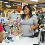 Customers Ashley Mendiola, center, and Rebekah Borden prepare to pay for a purchase in the Twinkles store at the Guam Premier Outlets on May 15.