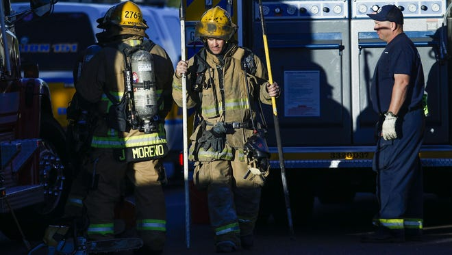 Glendale firefighters pack up their gear after responding to a fire and shooting scene near 48th Avenue and Cactus Road on Tuesday, Feb. 23, 2016, in Phoenix.