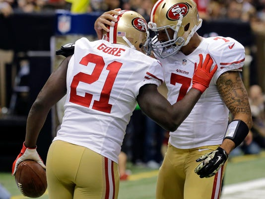 San Francisco 49ers running back Frank Gore (21) is congratulated by quarterback Colin Kaepernick (7) after scoring on a touchdown carry in the first half of an NFL football game against the New Orleans Saints in New Orleans, Sunday, Nov. 9, 2014. (AP Photo/Bill Haber)