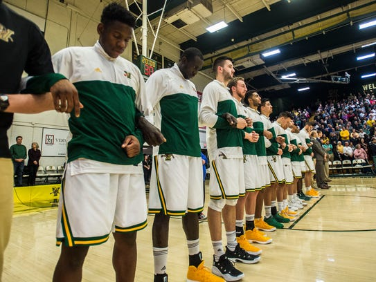 The University of Vermont men's basketball team lock arms during the national anthem before Wednesday night's game against UMFK.