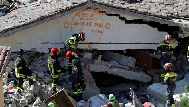 Rescuers mark a building with paint signaling the date and time of start and end of the search operation on that building, following Wednesday's earthquake in Pescara Del Tronto, Italy, Thursday, Aug. 25, 2016. Rescue crews raced against time Thursday looking for survivors from the earthquake that leveled three towns in central Italy, but the death toll rose to 247 and Italy once again anguished over trying to secure its medieval communities built on seismic lands.