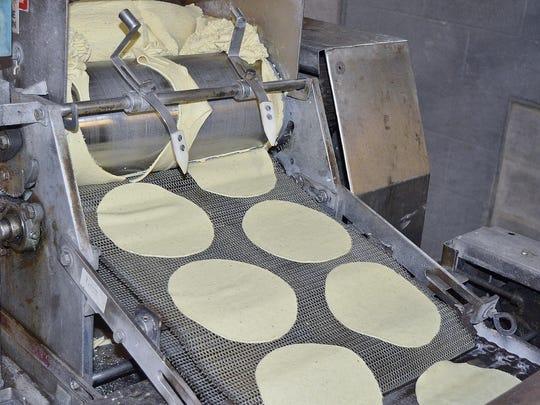 A machine cuts flattened masa — corn-based dough —