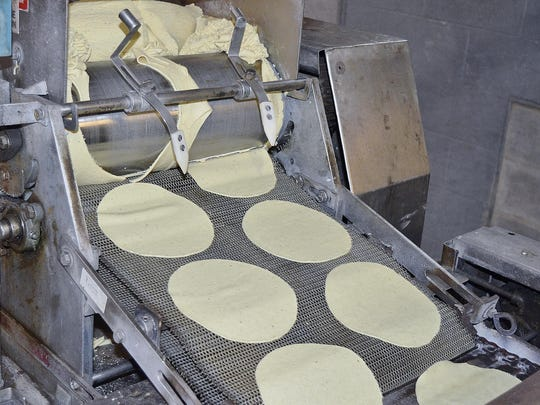A machine cuts flattened masa — corn-based dough — into circles before a conveyor belt takes them to an industrial oven where they're baked into tortillas at La Mejor del Valle restaurant and grocery store in Farmersville.