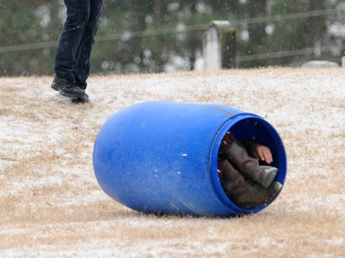 Shana Kendrick, left, laughs as her cousin, J.J. Kendrick, rolls down the hill in a barrel Tuesday during a winter storm.