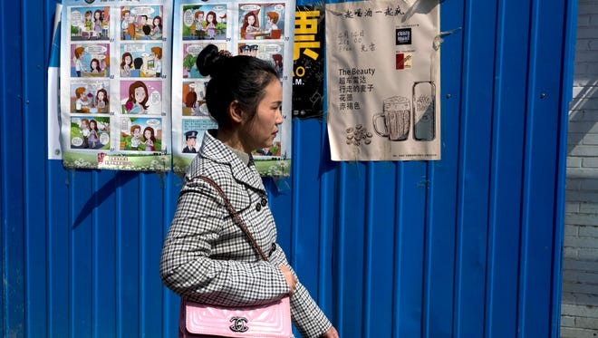 A woman walks past a poster warning against foreign spies displayed in an alleyway in Beijing on  April 20, 2016.