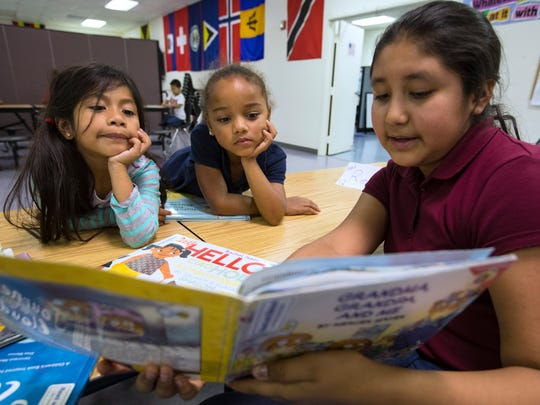 Gloria Estrada, 11, a student at the African Caribbean American Center (AFCAAM) in Fort Myers, helps read to younger students Ayhana Santos-Soto, left, and Aracely Vasquez, both 6 as part of their reading exercises.
