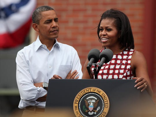 First lady Michelle Obama speaks during a stop on Wednesday, Aug. 15, 2012, in Dubuque, Iowa, as President Barack Obama looks on.