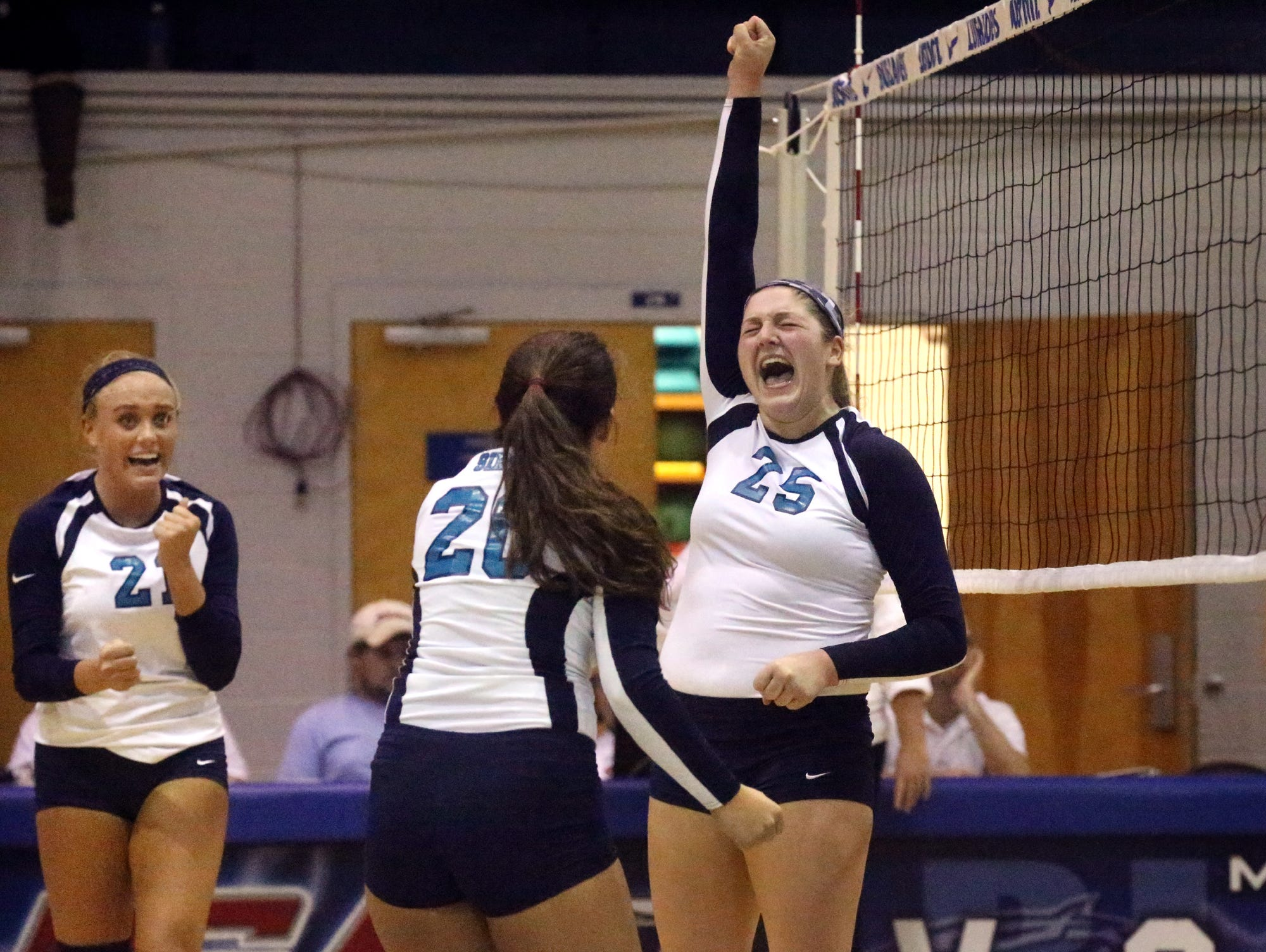 Siegel's Leah Poarch (21), Kristin Demonbreun (20) and Katelyn Lester (25) celebrate a point during the second round of the TSSAA Class AAA state volleyball tournament against Bearden Wednesday at MTSU.
