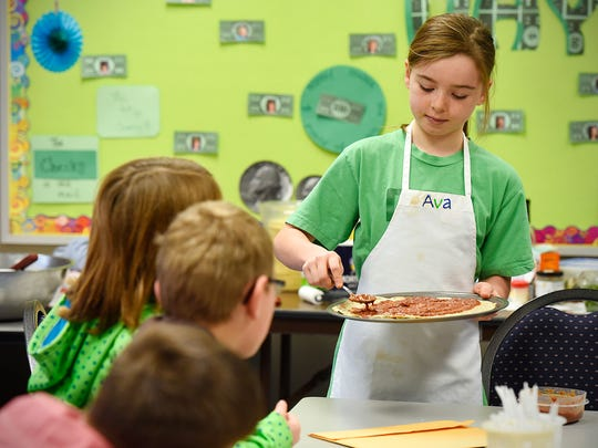 Monticello fourth-grader Ava Nebben demonstrates how she makes her pizza to classmates during a cooking demonstration Monday, Dec. 14, at  Little Mountain Elementary School in Monticello. Nebben was Minnesota's 2015 Healthy Lunchtime Challenge winner which won her a trip to the White House to meet the Obamas.