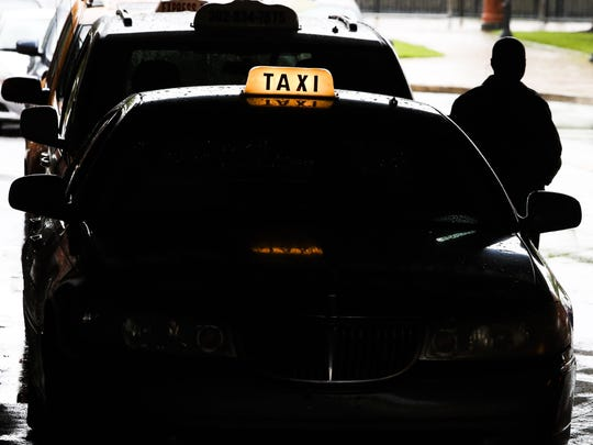 Taxis line up outside the Wilmington Train Station on May 6. Ride-sharing companies use third-party services that check the names and Social Security numbers of its drivers.