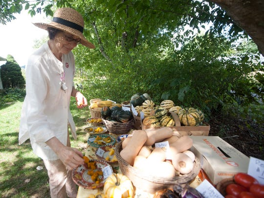 Anita Walling examines some of the produce on the tasting table at Full Sun Farm during a previous ASAP farm tour.