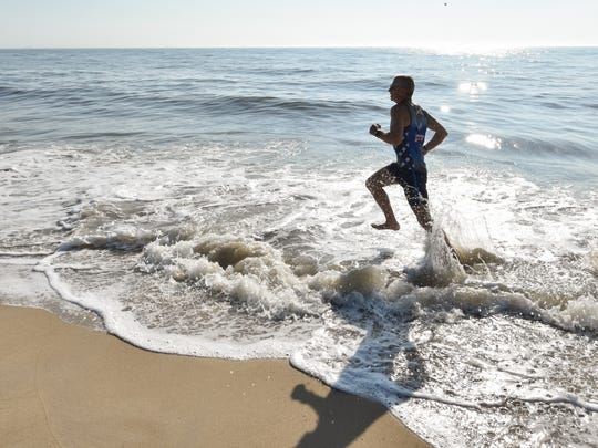 Bruce Clayton of Rehoboth runs through the waves at