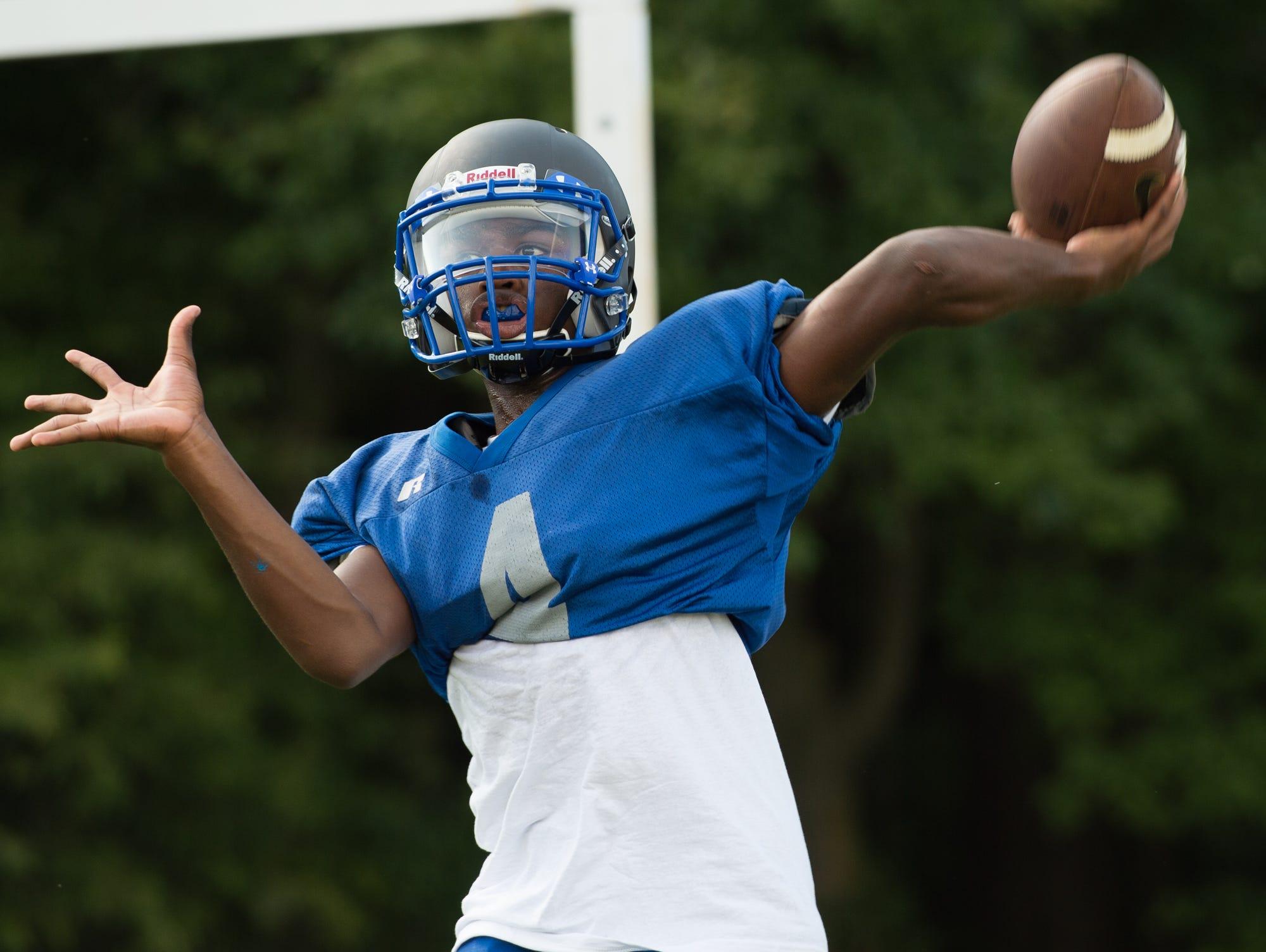 Woodbridge High School football quarterback Troy Haynes warms up his throwing arm during practice.