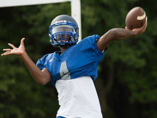 Woodbridge High School football quarterback Troy Haynes warms up his throwing arm during practice.