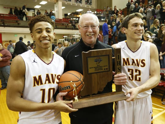 Robert Phinisee and Haden Deaton present McCutcheon head coach Rick Peckinpaugh with the trophy after the Mavericks defeated Zionsville 61-47 to win the Sectional championship Saturday, March 4, 2017, at Lafayette Jeff.