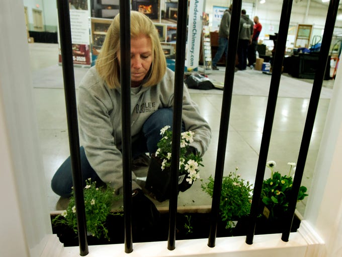 Lee Fence & Outdoor employee Tracy Stoner plants a