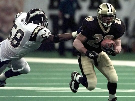 New Orleans Saints running back Troy Davis runs past San Diego Chargers linebacker Lew Bush (58) during first half NFL action Sept. 7, 1997, in the Louisiana Superdome in New Orleans.
