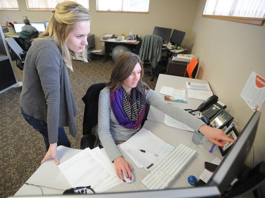 Jenny Knuth, left, and Ashley Puetz look at a project