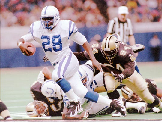 Colt running back Marshall Faulk (28) rushes for a 14 yard gain in the 2nd quarter as Saints defensive end Joe Johnson (94) pursues. Faulk rushed 17 times for 98 yards and 1 touchdown. (STAFF PHOTO/PAUL SANCYA)