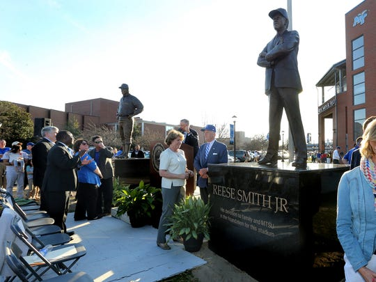 Family members of former MTSU baseball coach John Stanford and former baseball player and benefactor Reese Smith Jr. gather around newly unveiled statues of the men Tuesday in front of Reese Smith Jr. Field.