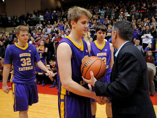 Guerin Catholic forward Aaron Brennan is presented with the game ball after losing to Greensburg during the Class 3A Semistate game, Saturday at Richmond High School. Greensburg won the game 74-67.