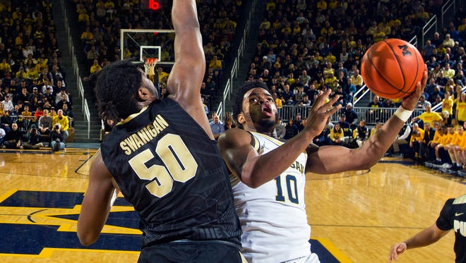 Purdue's Caleb Swanigan defends Michigan guard Derrick Walton Jr. in the first half of U-M's 82-70 win Feb. 25, 2017 at Crisler Center.