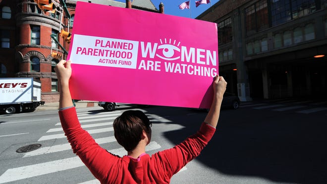 """Planned Parenthood employee Mackenzie Szymanski of Indianapolis holds a sign as she and supporters protested Congressman and gubernatorial candidate Mike Pence across from Union Station on Monday, September 24, 2012. The group was trying to raise awareness on Pence's position on issues that are important to Hoosier women and families outside his """"Roadmap for Indiana Rally"""" in downtown Indianapolis. (Matt Detrich / The Star)"""