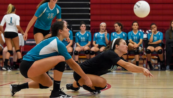 Jensen Beach's Shawna Smith (left) and Bella Moore dig the ball Tuesday, Sept. 5, 2017, during their team's high school volleyball game against St. Lucie West Centennial at St. Lucie West Centennial High School in Port St. Lucie. To see more photos, go to TCPalm.com. CQ: Shawna Smith, Bella Moore