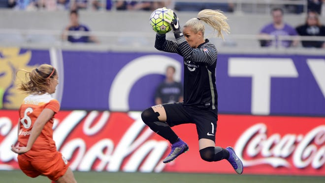 Ashlyn Harris of Orlando makes a stop before Houston's Morgan Brian can take advantage during Saturday's home opener in Orlando.