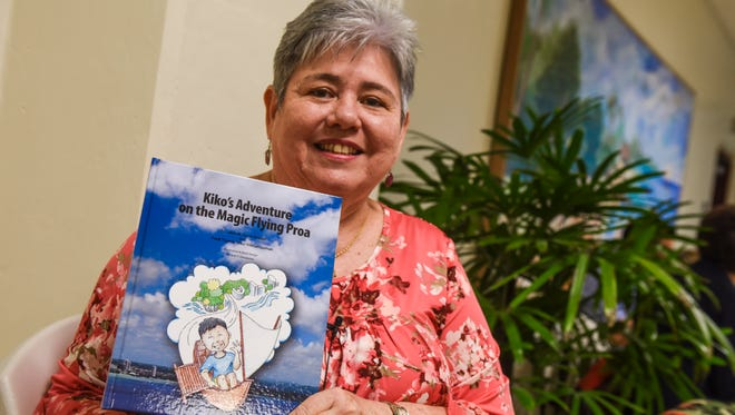 """Chamorro author and scholar, Laura Torres Souder, displays a copy of the children's storybook """"Kiko's Adventure on the Magic Flying Proa"""" she wrote with her grandnephew Frank Thomas """"Kiko"""" Freitas Guzman, during a launch of the book at the Guam Museum in Hagåtna on Saturday, Nov. 25, 2017."""