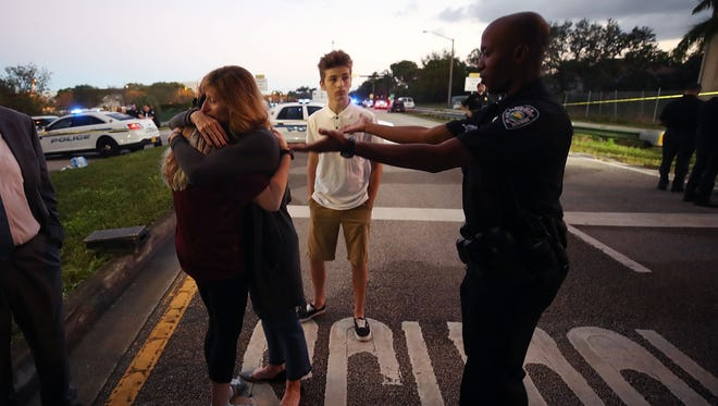 Kristi Gilroy hugs a young woman as a police officer tries to clear a closed road at a police checkpoint near Marjory Stoneman Douglas High School where 17 people were killed by a gunman Feb. 15, 2018, in Parkland, Fla.  Police arrested the suspect after a short manhunt and have identified him as 19-year-old former student Nikolas Cruz.