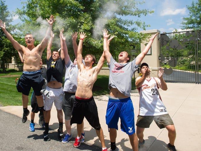 Cleveland Cavaliers basketball fans celebrate in front of the house of LeBron James, in Bath, Ohio, after learning of James' decision to sign as a free-agent with the Cavaliers, Friday, July 11, 2014. The fans tossed powder in the air, like LeBron's pregame ritual.