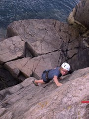 Ethan Burkett climbs a route at the Otter Cliffs in Acadia National Park in Maine during the summer of 2015.