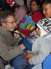 Pediatrician Barry Finette examines a child in Cusco, Peru, during a trip to field test the Medsinc medical intelligence platform being developed by his company, THINKmd.