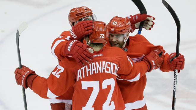 Detroit Red Wings center Andreas Athanasiou (72) is congratulated by Dylan Larkin and Henrik Zetterberg, right, on Feb. 23, 2016, in Detroit.