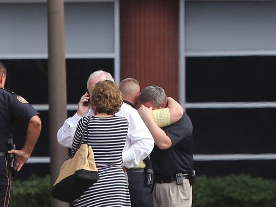 Law enforcement officers comfort each other outside Memorial Hospital at Gulfport in Gulfport, Miss., on Thursday after Bay St. Louis Police Chief Mike De Nardo died. Hancock County Coroner Jim Faulk said Chief  DeNardo died Thursday.