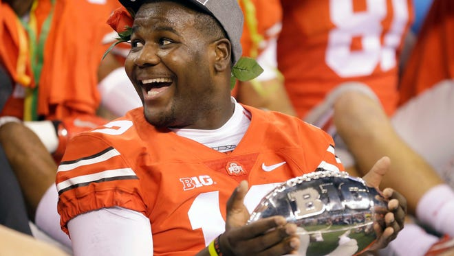 Ohio State quarterback Cardale Jones holds the championship trophy following the Big Ten Conference championship NCAA college football game against Wisconsin after midnight Sunday in Indianapolis. Ohio State won 59-0.