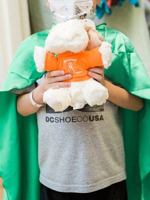 A sick child receives a donated Bedside Healer. Bedside Healers are stuffed animals with Velcro straps on the back so patients can attach them to their beds, IV stands or wheelchairs.