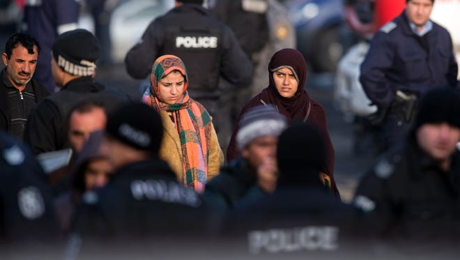 Migrants walk among Bulgarian riot policemen inside the Harmanli Refugee center, near the Bulgarian border with Turkey on November 25, 2016.