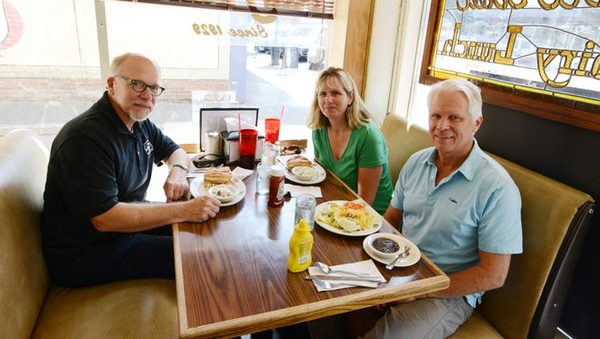 """Rick Bastasch (left), Michelle Cordova and Jim Green of Straub Environmental Center share information about the upcoming """"From Cart to Art"""" competition during Holding Court at the Court Street Dairy Lunch on Tuesday, Aug. 19, 2014."""