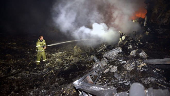 A firefighter sprays water on the wreckage of the Malaysian airliner on Thursday.