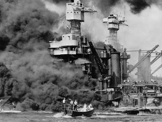 In this photo from Dec. 7, 1941, a small boat rescues a seaman from the burning USS West Virginia in Pearl Harbor, Hawaii, after Japanese aircraft attacked the military installation. More than 2,300 U.S. service members and civilians were killed in the strike that brought the United States into World War II.