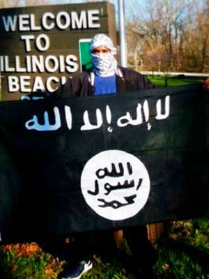 In this undated photo provided by the Federal Bureau of Investigation, Joseph D. Jones poses with an Islamic State group flag at Illinois Beach State Park in Zion, Ill.  Jones and Edward Schimenti were arrested by FBI agents on Wednesday, April 12, 2017 on terrorist charges for allegedly conspiring to support the Islamic State militant group.