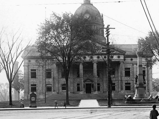 A New York weather kiosk can be seen on the left in front of a courthouse, around 1920.