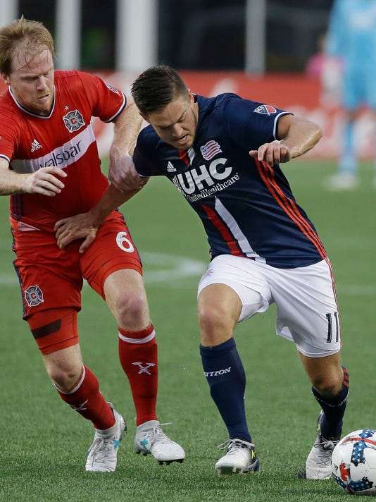 New England Revolution midfielder Kelyn Rowe (11) fends of Chicago Fire midfielder Dax McCarty (6) as Rowe makes a move to the goal during the first half of their MLS Soccer match, Saturday, June 17, 2017, in Foxborough, Mass. (AP Photo/Stephan Savoia)